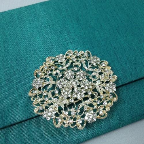 Large flower rhinestone brooch for wedding embellishment shown on a silk envelope