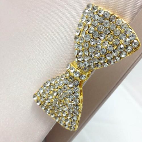 Large golden bow brooch on blush pink silk invitation