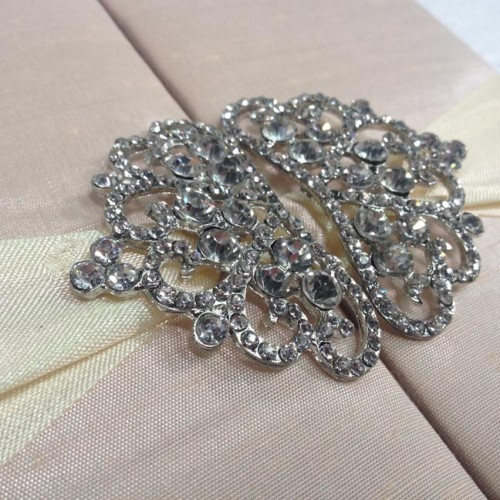 Detail view of silver plated crown brooches with rhinestones on blush pink folio invitation
