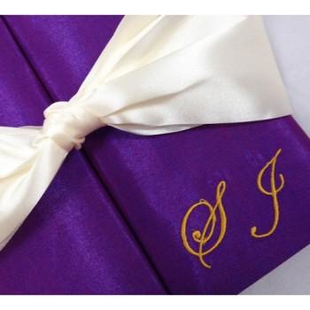 Monogram embroidery and ribbon bow on gatefold wedding invitation box