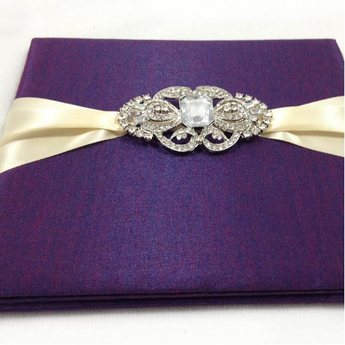 Rhinestone brooch on purple silk invitation
