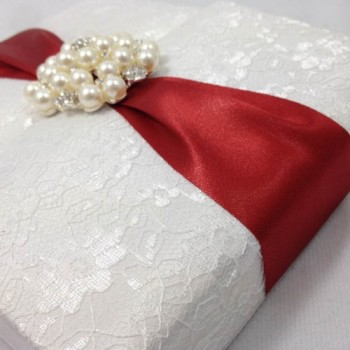White lace box with red ribbon and large pearl brooch