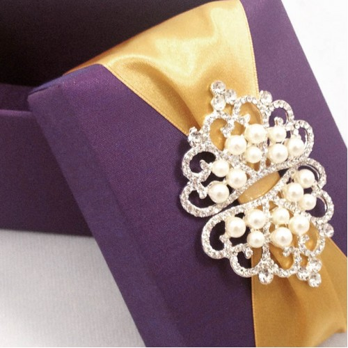Detail view of purple silk box with golden ribbon and crown brooches
