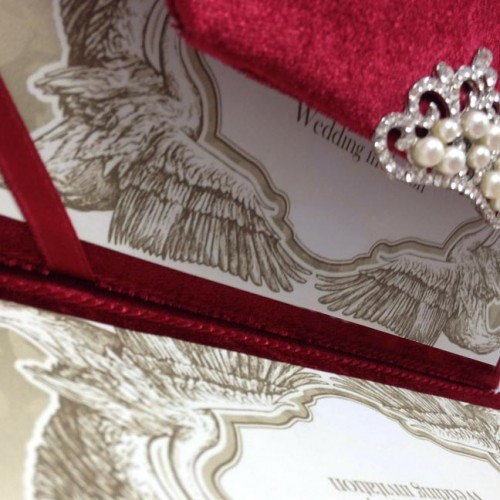 red velvet envelope opened with wedding invitation card