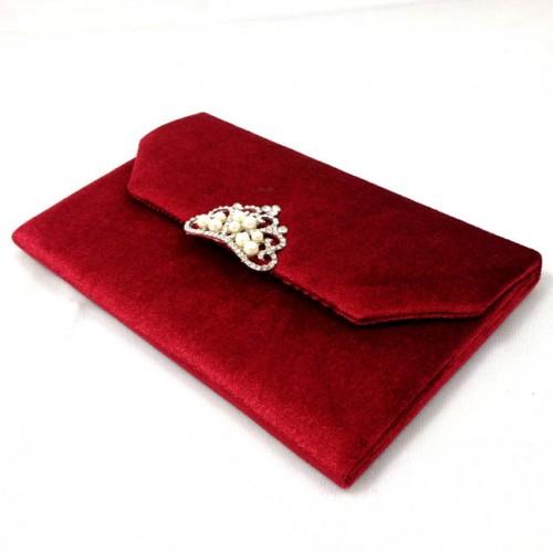 Side view of velvet envelope with pearl crown brooch