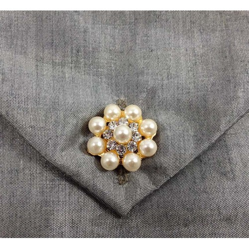 Close-up view of pearl button on silk envelope