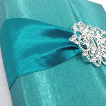 Detail view of our luxury silk wedding invitation box featuring rhinestone crown brooches