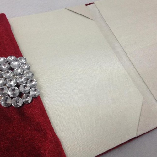 Red velvet invitation folder for wedding cards featuring rhinestone brooch