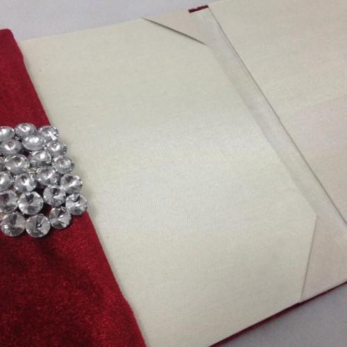 Red velvet invitation folder for wedding cards featuring rhinestone brooch