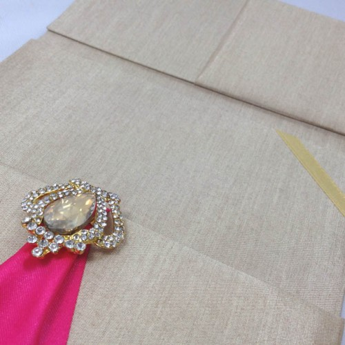 Gold crown brooch on silk invitation