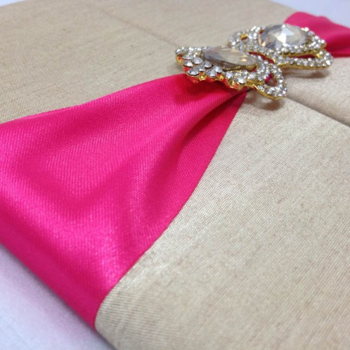 Wedding invitation folio in gold with deep pink ribbon and gold crown brooch