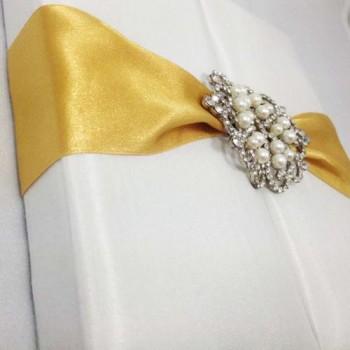 White gatefold box with golden ribbon