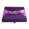 Plum color boxed wedding invitation with violet ribbon and crown brooches