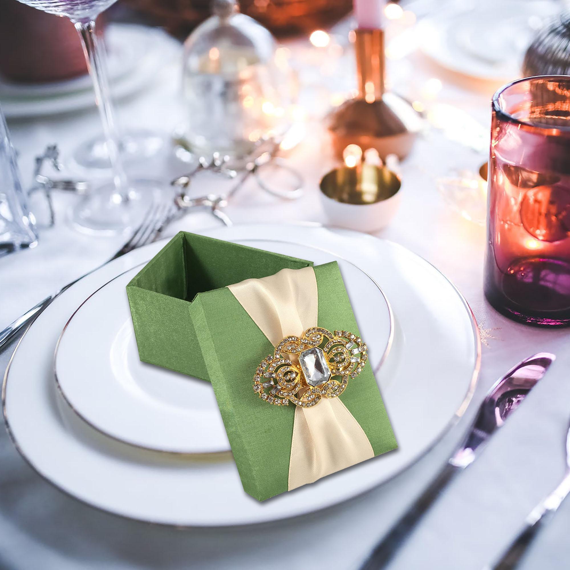 Presentation of green silk favor box on wedding table