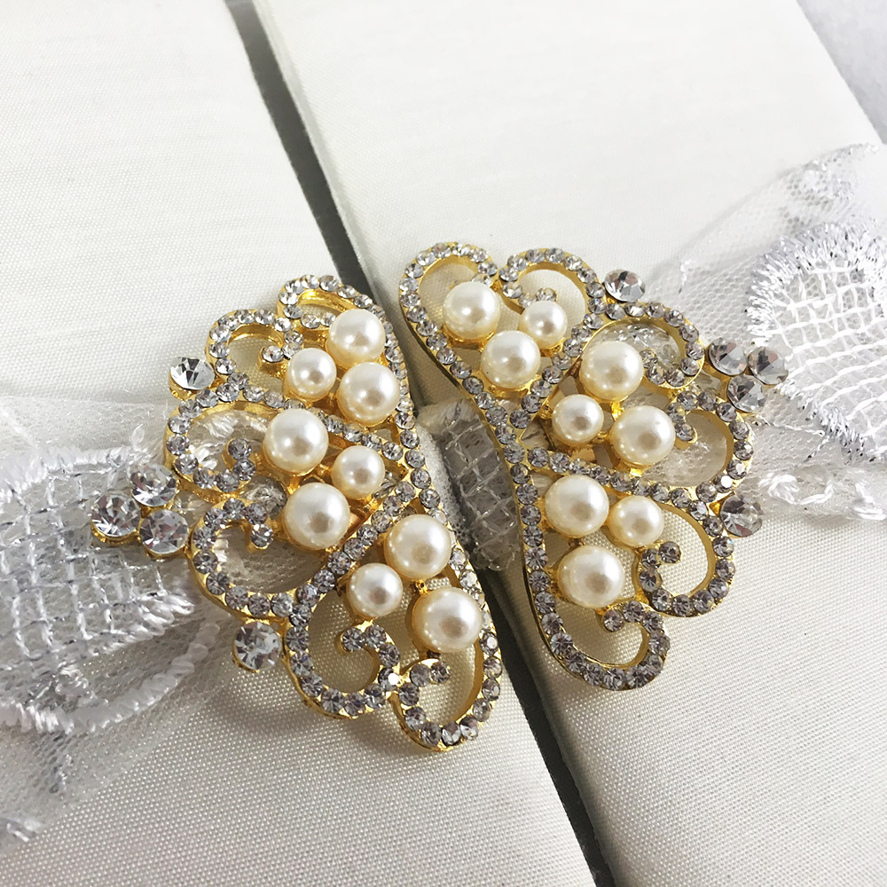 Close-up of gold plated brooch with pearls