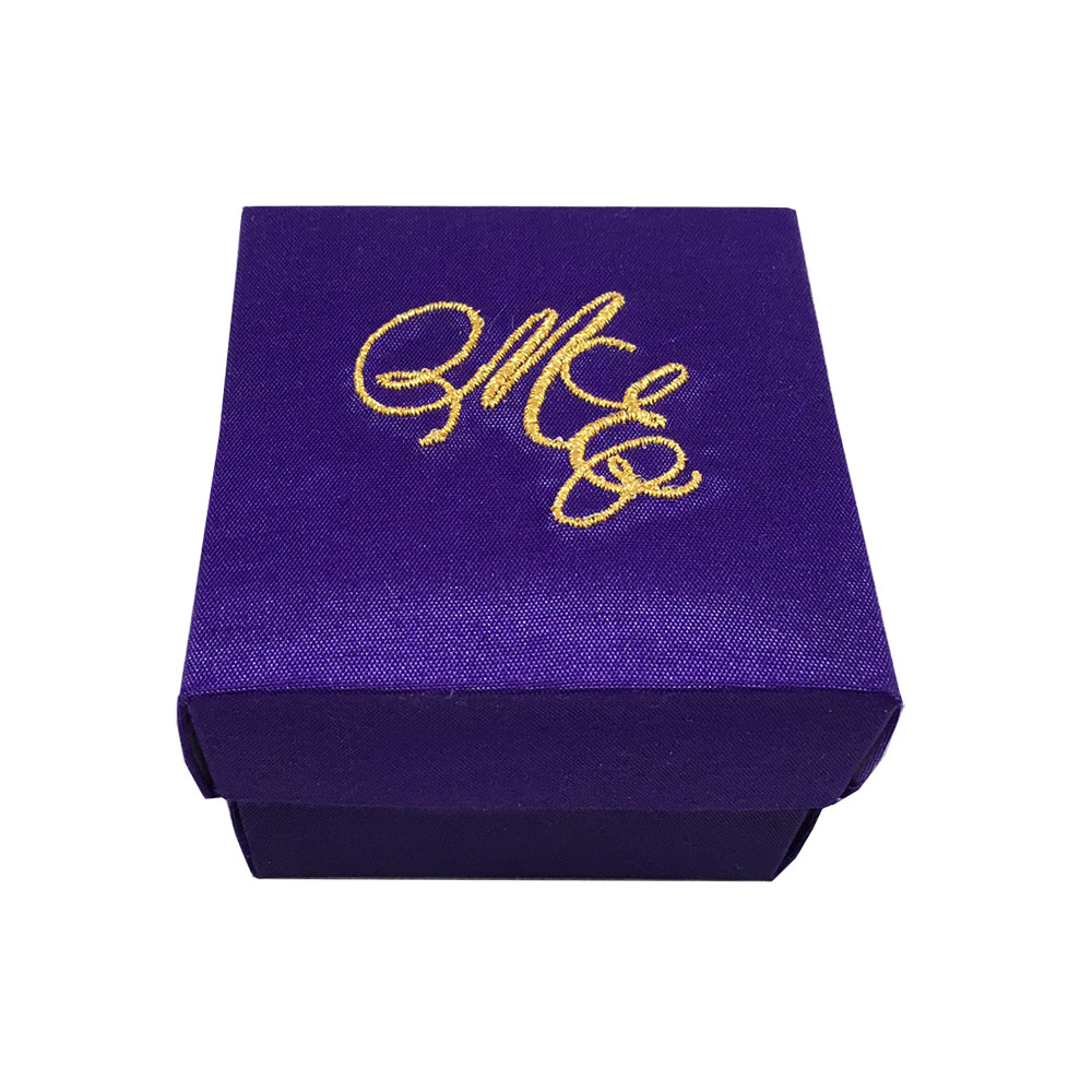purple wedding favour box with golden monogram embroidery