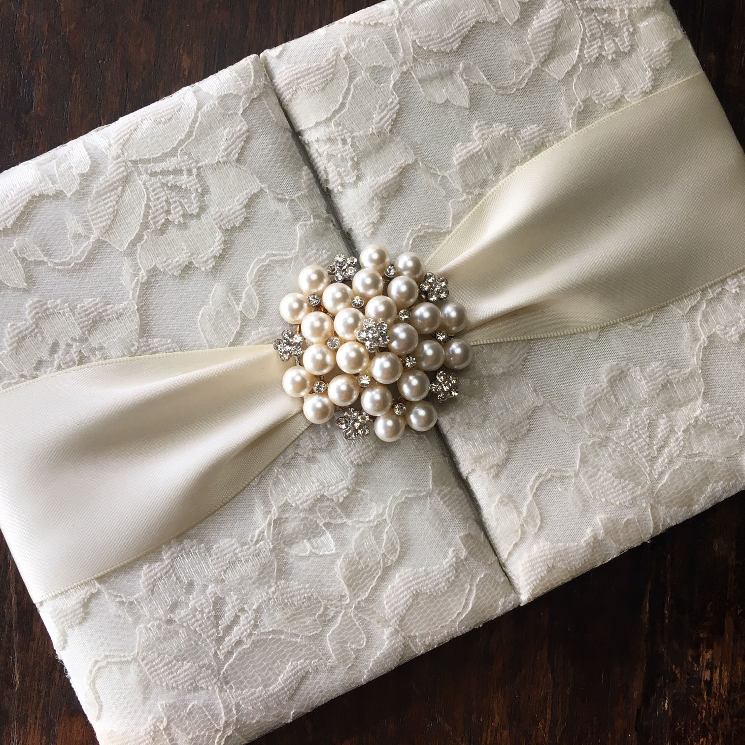 lace wedding invitations with pearl brooch and ivory lace fabric