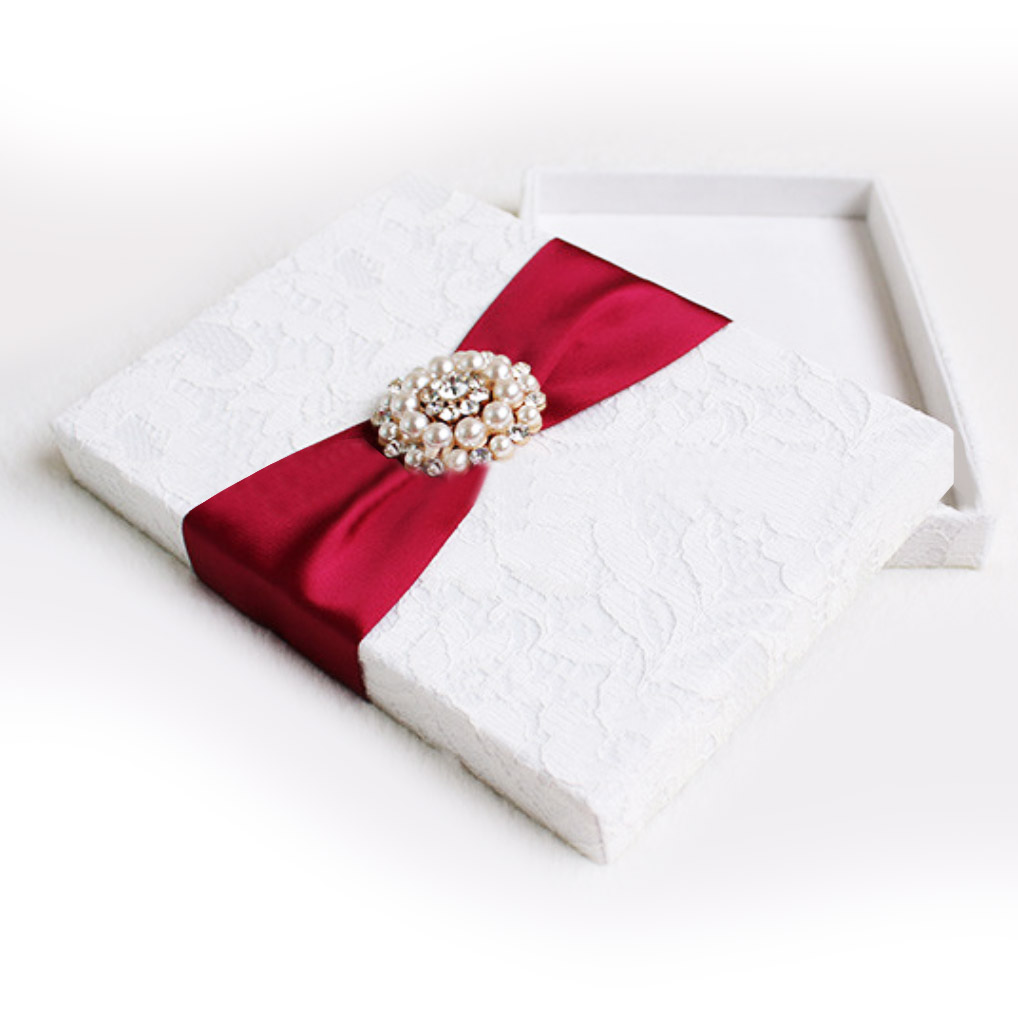 white lace wedding box with red ribbon and pearl brooch